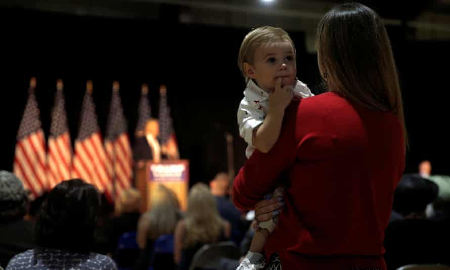 A woman holds her son as Donald Trump speaks.