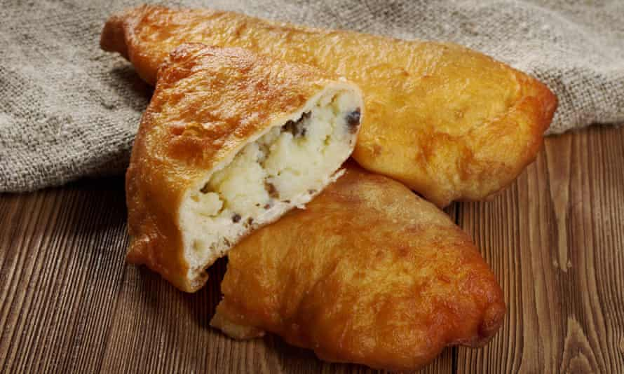A piece of chebureki, a traditional Tatar dish of deep-fried half-moon pies filled with meat or cheese.
