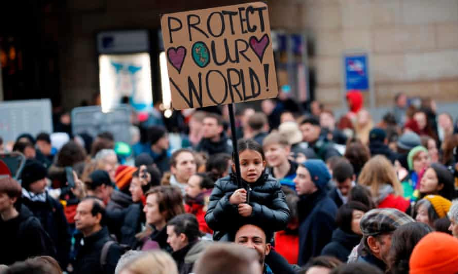 A child holds a placard during a protest against governmental inaction towards climate breakdown and environmental pollution in Lausanne, Switzerland, days before the start of the Davos summit.