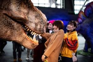 Tokyo, Japan. Members of the media meet a moving model of a Tyrannosaurus