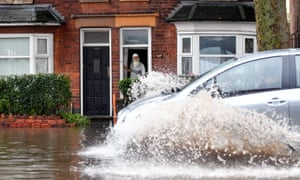 A man watches a car drive through a flooded street in Alum Rock, Birmingham.