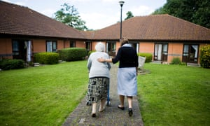care worker and elderly person outside care home