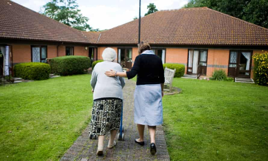 Care home worker looking after elderly resident