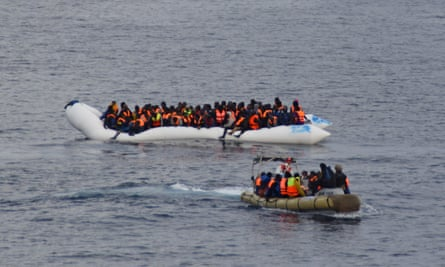 Migrants in a dinghy wait to be rescued