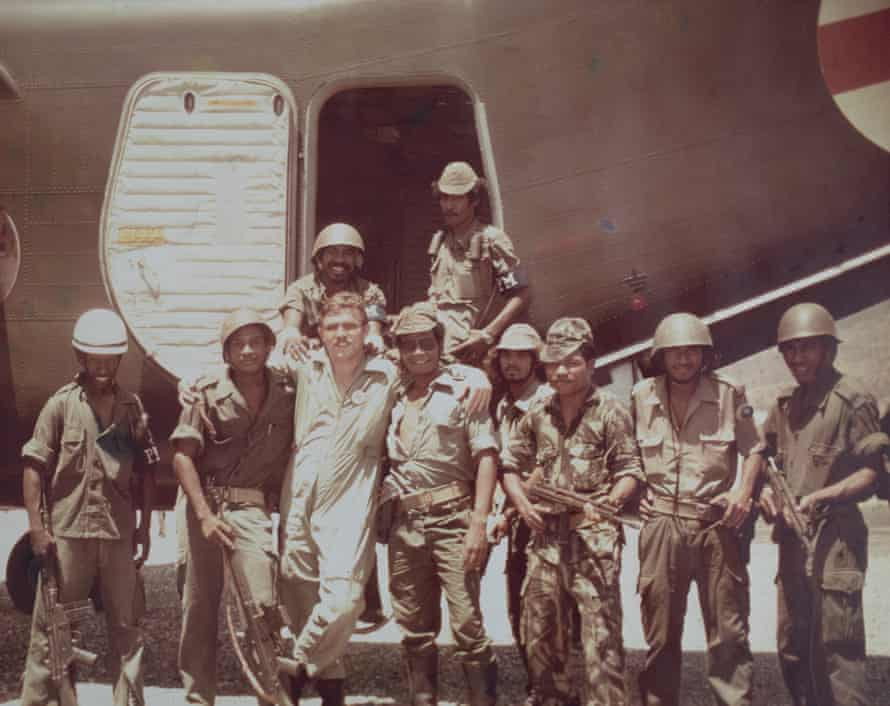 Copypix - Keirman French with Fretilin fighters at Dili airport, 1975. Photo, Pilot Officer, Gordon Browne. In 1975, during a civil war in East Timor, armed soldiers forced their way onto a Caribou plane and demanded that women and children be taken to Australia. About 50 people were flown on the plane, which was only able to normally carry 32 passengers. Keirman French, the pilot, remembers being threatened at gunpoint by one of the soldiers.