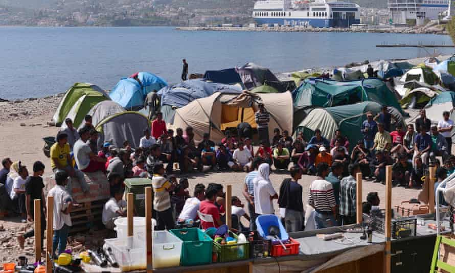 Migrants gather for a meeting at an unofficial camp run by volunteers near the port of Mytilene on the island of Lesbos
