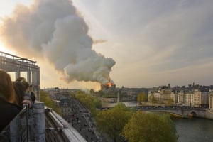 Flame and plumes of smoke rise from Notre Dame cathedral as it burns in Paris