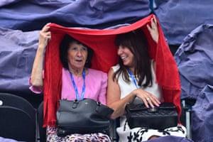 Eastbourne, England: Spectators shelter under a shawl as rain delays play between Novak Djokovic and Vasek Pospisol at the ATP Aegon tennis tournament