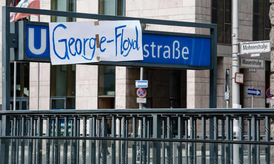 Campaigners cover up the name of Mohrenstrasse station in Berlin with a George Floyd banner.