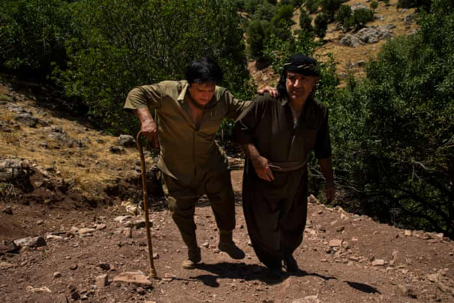 Landmine deminer Hoshyar Ali climbs a hill with his brother, Rizgar Ali, supporting him near Penjwen, Iraqi Kurdistan. They climbed the hill to view a suspected minefield after a farmer called and said he's lost more than 10 livestock to landmines in the area.