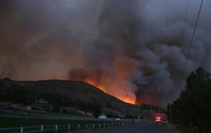 An emergency vehicle drives down Twisp River Road as a wildfire burns over the hillside
