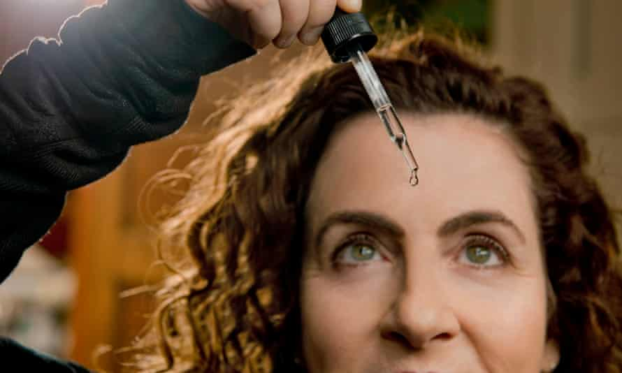Ayelet Waldman with a pipette of drugs over her forehead