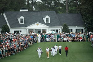 Tiger Woods, Francesco Molinari and Tony Finau – the final group of the day – walk up the first fairway after teeing off. Molinari (-13) holds a two-shot lead over his playing partners.