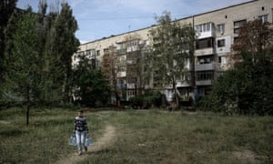 A local woman carries water for her family in the city of Luhansk