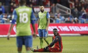 Jozy Altidore reacts after being brought down as Clint Dempsey watches on.
