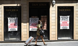 """A closed men's clothing shop, on which placards read """"Without government aid we can not reopen on May 18, thousands of employees at risk"""" in Rome."""