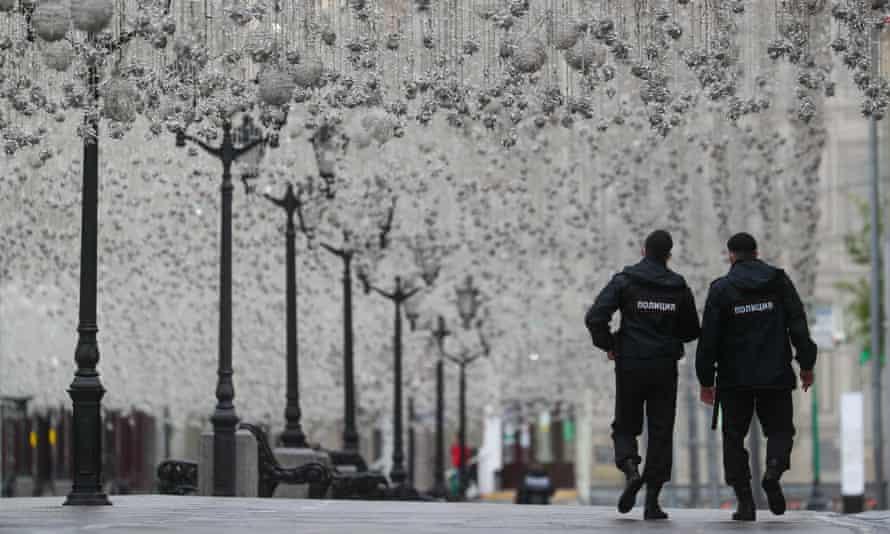 Police officers patrol a deserted Nikolskaya Street in Moscow.
