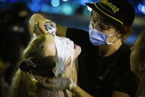 A person pours milk on the face of a protester who was teargassed by police officers in New Orleans