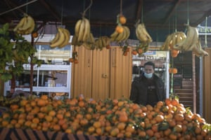 A fruit vendor wearing a face mask waits for clients in a daily market in Dakhla