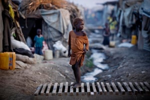 A young child crosses a stream full of dirty water in Malakal camp