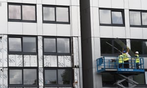 Workers remove cladding from a tower block in June 2017.