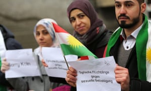 Refugees from Syria in Germany carry signs saying 'Syrian refugees against sexual harassment'