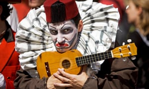 Street performer wearing a fez and carrying a ukelele.  The Fourth Monkey Theatre Company try to drum up business. Performers try to sell their shows to punters on the Royal Mile - at the Edinburgh festival fringe.