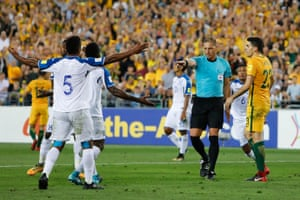 The referee points to the spot, awarding Australia a controversial handball decision. The Hondurans are incensed – no-one seems to know the cause. Apparently it's a handball.