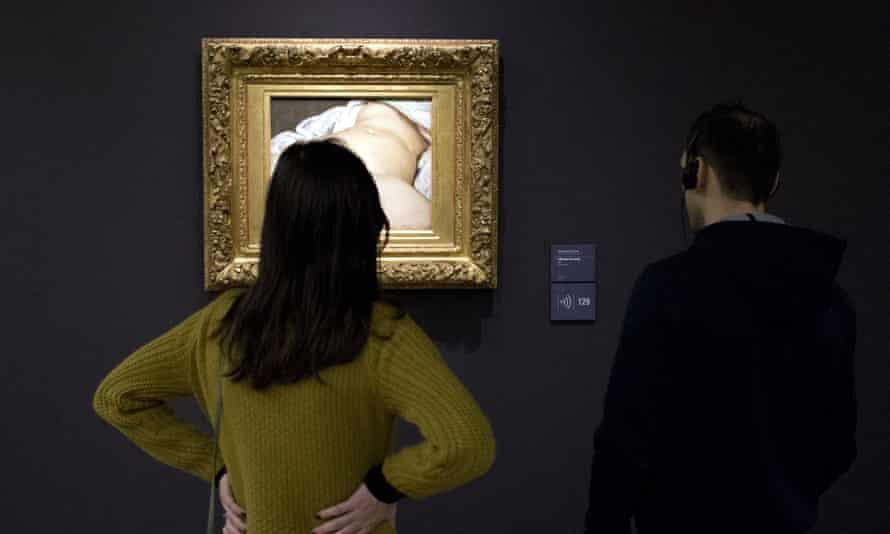 Visitors view Gustave Courbet's painting at the Musée d'Orsay.