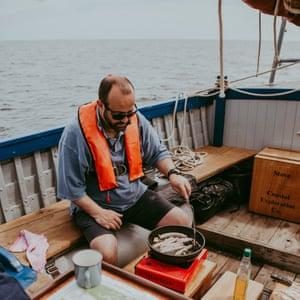 Chef Charlie Hodson prepares cooked breakfast on board the Salford whelk boat, Norfolk, UK.