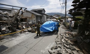 Rescue workers carry Yumiko Yamauchi, 93, on a stretcher covered in a blue plastic sheet, as they tread their way through rubble in Mashiki