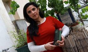 Israeli author Dorit Rabinyan poses with her Hebrew-language novel Gader Haya.
