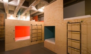 Plywood walls with gaps and ladders to cubbyhole beds