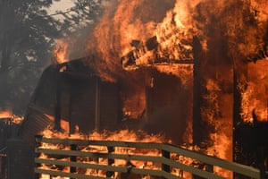 Fire burns a home in Buxton, New South Wales, as temperatures above 40C and strong winds fan a number of fires around Sydney