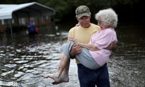 Bob Richling carries Iris Darden, 84, out of her flooded home as her daughter-in-law, Pam Darden, gathers her belongings in the aftermath of Hurricane Florence in Spring Lake, North Carolina, Monday.