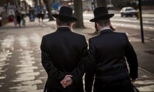 Jewish men walk in Stamford Hill, London.