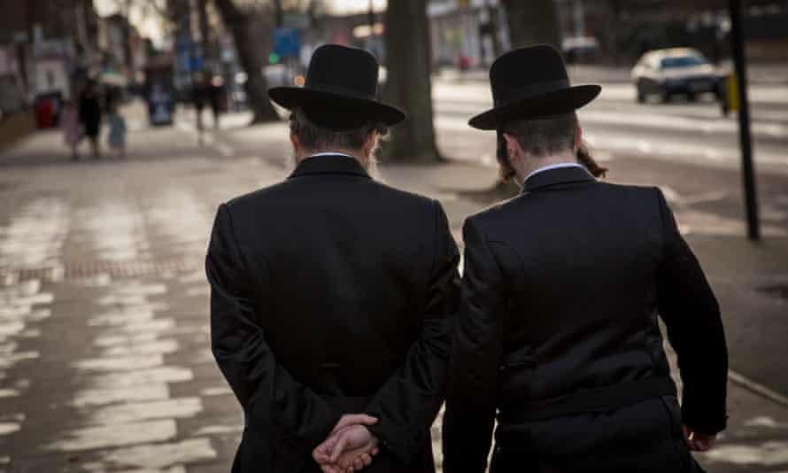 Two men in black hats, black coats and peyot walk along a pavement in Stamford Hill, London
