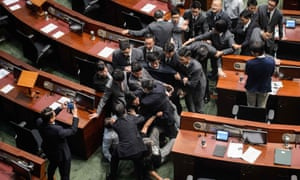 Newly elected lawmaker Baggio Leung (centre, wearing glasses) is restrained by security after attempting to read out his oath at the Legco.