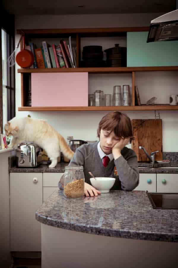 A boy falling asleep in front of his breakfast
