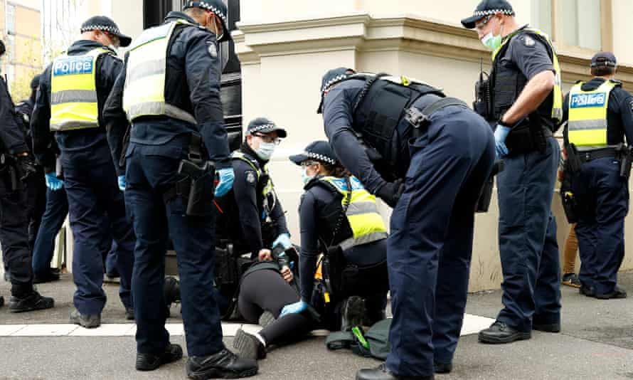 Police detain a women in Melbourne near the CFMEU building on Wednesday morning.