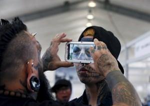A tattoo artist takes a photo of an eyeball tattoo