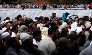 A woman takes photo with her mobile phone of people attend the Friday prayers at Hagley Park outside the mosque.