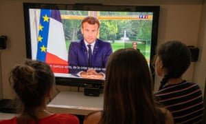 Members of the public watching Macron give a previous address, in June.
