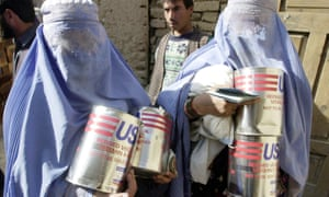 Two Afghan women carry cans of cooking oil provided by US Aid in Kabul on Wednesday, 21 November 2001