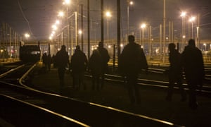 Refugees walk on the railway tracks leading to the entrance of the Channel tunnel in Calais.