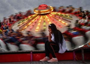 A girl waits next to people riding a merry-go-round in Țăndărei
