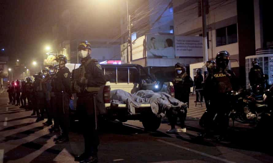 Police officers stand guard near two bodies outside of a nightclub in Lima, Peru.