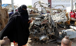 a woman walks past the wreckage of a bomb blast in Mogadishu