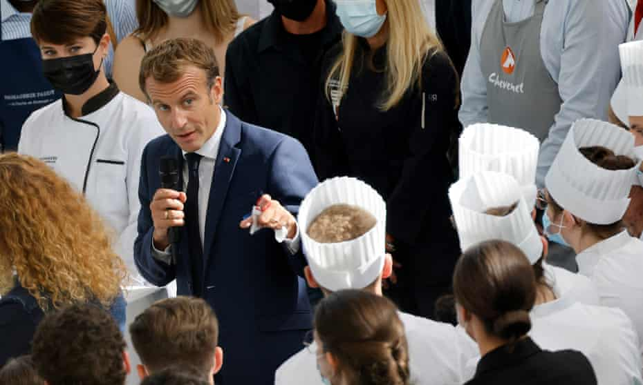 Emmanuel Macron holds microphone and gestures