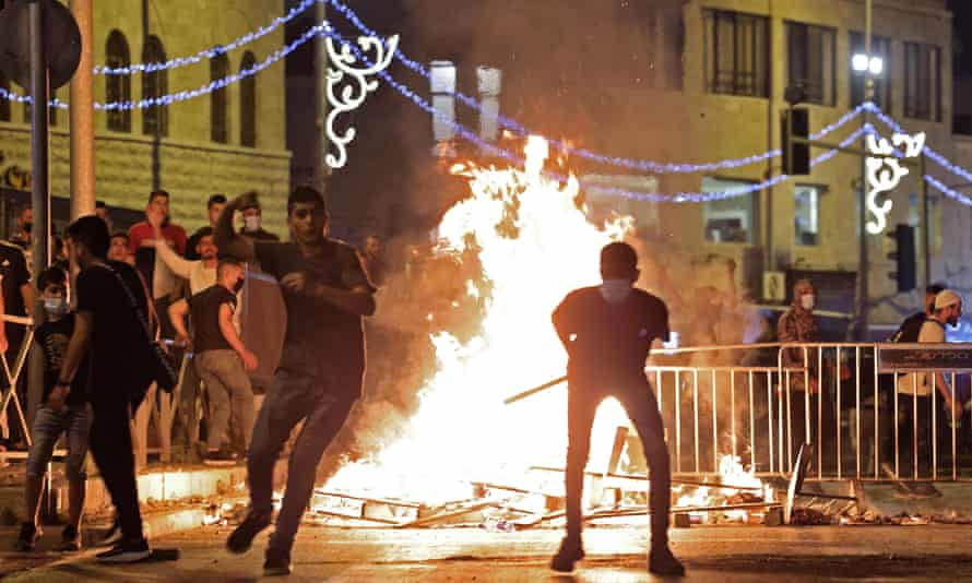 silhouettes of people against a blazing fire and metal barricades, at night